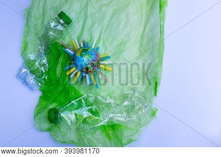 Global Warming Pollution. Blue Plastic Globe Is Inserted With Piece Of Plastic Tube In Middle. World