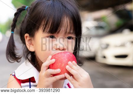 Head Short Of Cute Girl Is Biting At A Red Apple. Children Eat Fruit. Asian Girl Uses Two Hands To H