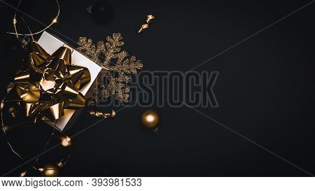 Gift Boxes Background. White Gift Box With Golden Ribbon, New Year Balls And Sparkling Lights Garlan