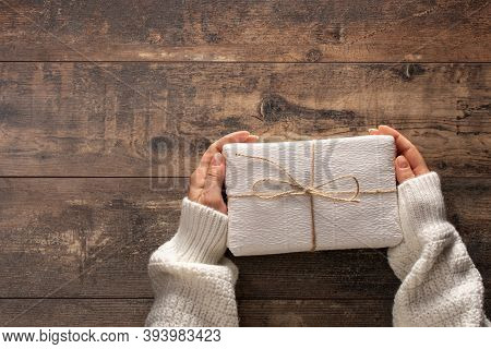 Woman Holding Christmas Gift Box. Wooden Rustic Table. Top View Woman Hands Holding Present Box. Fem