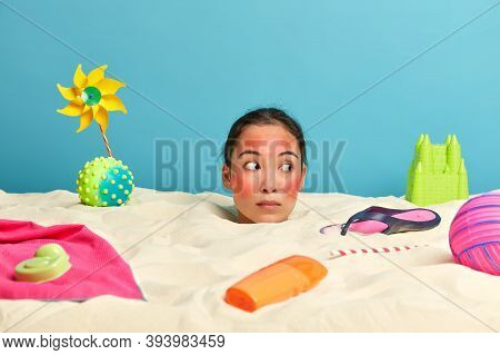 Sea Resort And Tourism Concept. Surprised Woman Looks Away, Keeps Head Over Beach Sand, Has Red Skin