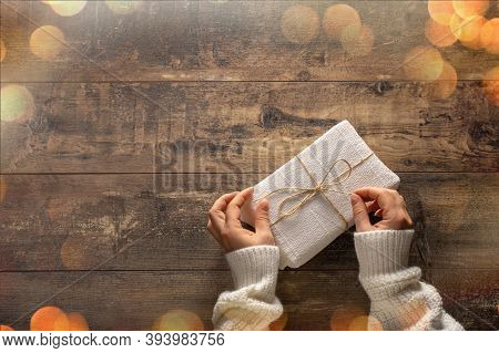Woman Hands Unpacking Gift Box On Rustic Wooden Table. Holiday Bokeh Lights. Christmas, Birthday Or