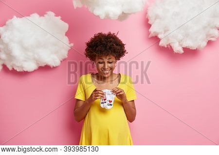 Expectant Mother With Glad Expression Looks At Small Babys Socks, Awaits For Child Birth, Dressed In