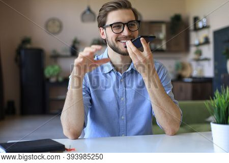 Confident Business Man In Glasses Holding Smartphone Near Mouth For Recording Voice Message Or Activ