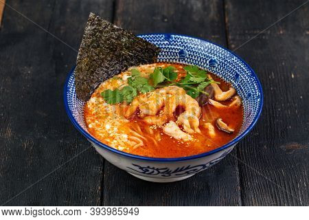 Tom Yam Ramen Noodle Soup With Seafood On The Dark Wooden Table