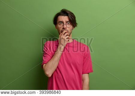 Portrait Of Scared Shocked Caucasian Man Keeps Hand On Mouth And Stares With Frightened Look, Sees S