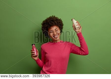 Isolated Shot Of Happy Pleased Afro American Woman Poses With Vegetarian Milk And Smoothie, Enriches