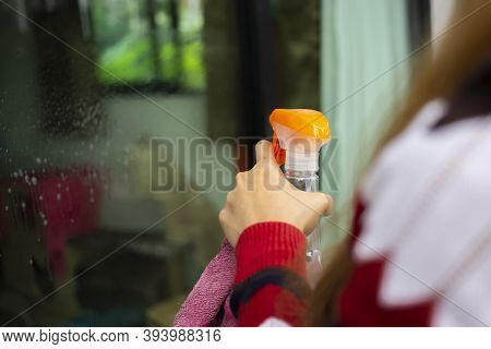 The Housekeeper Is Using A Glass Brush To Clean The Glass With Water Droplets. Green Wipe Glass On T