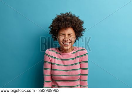 Joyful Optimistic Woman Hears Hilarious Joke, Closes Eyes And Smiles Broadly, Amused By Silly Anecdo