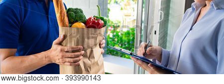 Asian Deliver Man In Uniform Handling Bag Of Food Vegetables And Greens To Customer At Door Home, Fo