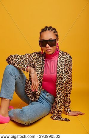 Photo Of Dark Skinned Lady In Trendy Sunglasses And Leopard Shirt, Poses On Floor Against Yellow Bac