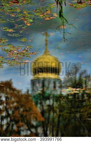 Reflection Of The Domed Dome Of The Russian Orthodox Church In The Water With Autumn Leaves