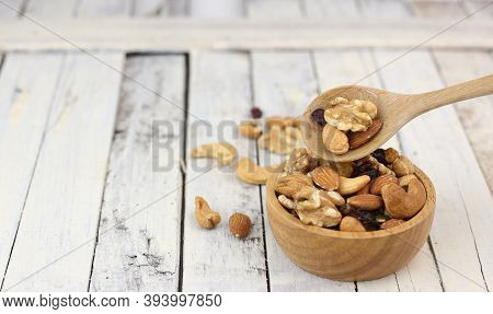 Many Healthy Nuts On Wooden Spoon Against White Wood