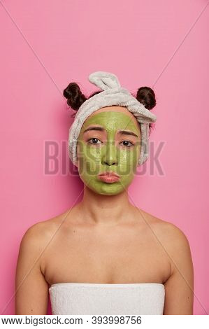 Sad Displeased Woman Gets Facial Care, Applies Green Mask On Face, Looks Unhappily At Camera, Tired
