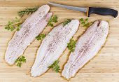 Three skinless fillets of white fish on natural bamboo board with Fillet Knife poster