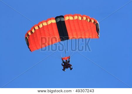 Skydivers Parachuting Down To The Earth In Tandem Jump