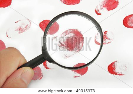 Magnifying glass in hand and fingerprints on white background