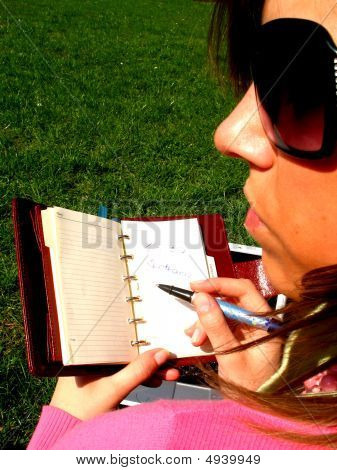 Girl With Notebook Sitting On The Grass