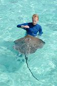 A tourist playing with and feeding a stingray Himantura fai in the shallow clear water of the lagoon of Bora Bora an island in the Tahiti archipelago French Polynesia. poster