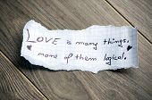 Love is many things none of them logical (Quote by William Goldman) - Hand writing text on a piece of paper on wood background poster