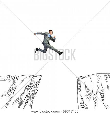 Young businessman jumping over drawn mountain gap