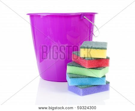 Pile Of Colorful Sponge Scourer And Pink Bucket Over White Background