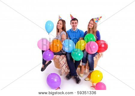 Three Friends Sitting On A Couch With Balloons And Hats