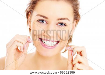 A picture of beautiful woman using a floss for her teeth over white background
