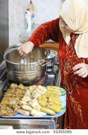 DAHAB, EGYPT - FEBRUARY 2, 2011: Egyptian woman prepares traditional meal. Egyptian food is a mixture of all the different civilisations that came to Egypt in the history of its existence.