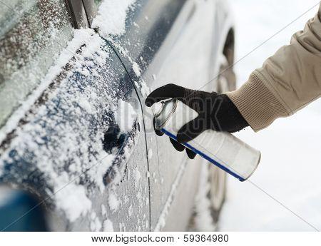 transportation, winter and vehicle concept - closeup of man hand with lock door de-icer