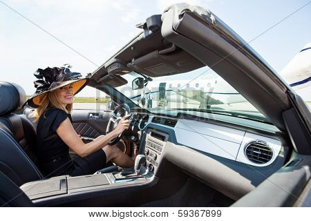 Portrait of woman driving convertible towards private jet at airport terminal