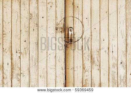Textured wooden door of an abandoned barn with a metal lock and handle poster