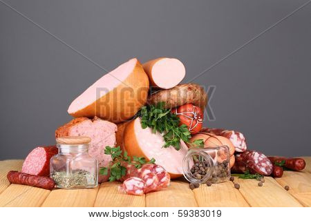 Lot of different sausages on wooden table on grey background poster