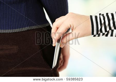 Pickpocket are stealing mobile phone from pocket, close up