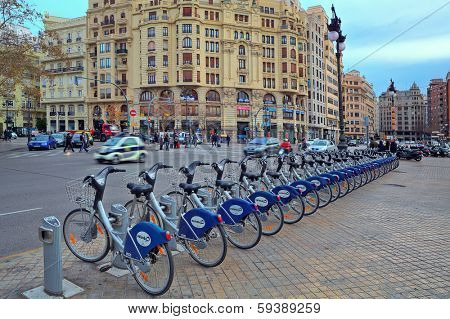 VALENCIA, SPAIN - JANUARY 14, 2014: City square and Valenbisi station - public bicycle rental station sponsored by city council is popular mode of transport with locals and tourists visiting Valencia.