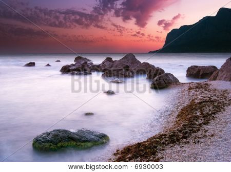 Dramatic sea sunset on a pebble beach with silhouetted mountain in the background