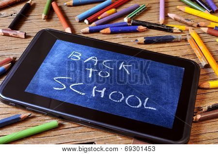 a tablet with a picture of a chalkboard with the sentence back to school written in it, on a rustic wooden desk with worn pencil crayons of different colors