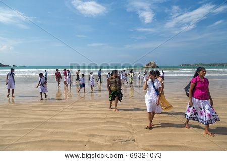 WELIGAMA, SRI LANKA - MARCH 7, 2014: Group of local people walking on sandy beach. Weligama is one of most popular Sri Lankan beaches,