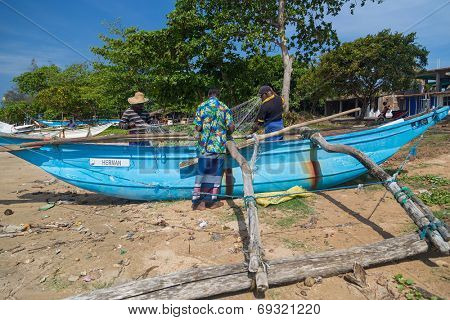 WELIGAMA, SRI LANKA - MARCH 7, 2014: Fishermen preparing fishing net. Tourism and fishing are two main business in this town.