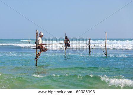 UNAWATUNA, SRI LANKA - MARCH 9, 2014: Stilt Fishermen at Unawatuna. Many of these fishermen earn more money posing for tourists than fishing fish.