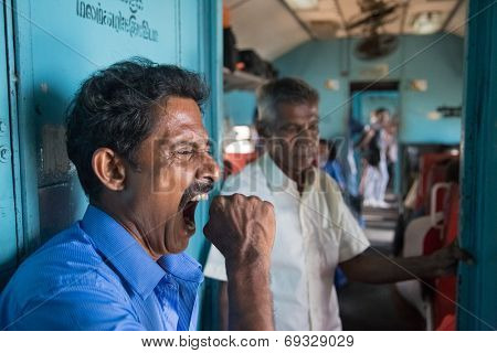 HIKKADUWA, SRI LANKA - MARCH 12, 2014: Local man yawning in train. Trains are very cheap and poorly maintained but it's the best option to witness a bit of everyday local life.