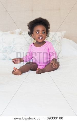 Baby girl in pink babygro sitting on bed at home in the bedroom