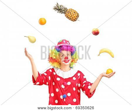 Female clown joggling a bunch of fruits isolated on white background