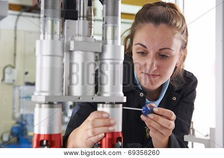 Engineer Working On Machine In Factory