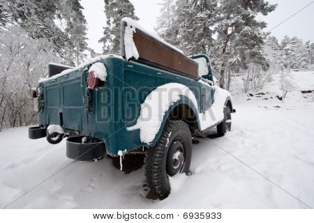 Snow-covered Car In Forest