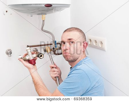 Inexperienced plumber trying to repair an electric water heater poster