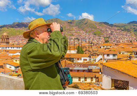 Senior tourist with binoculars watches citiscape in Cusco, Peru