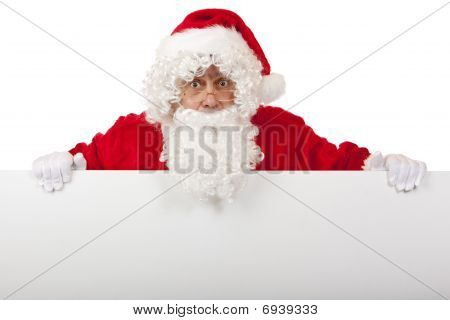 Surprised Santa Claus Is Holding A Christmas Advertisment Board In Hands.