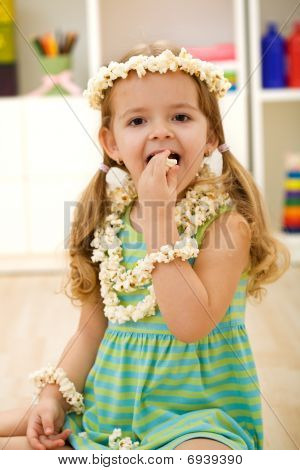 Happy Little Girl Eating Popcorn