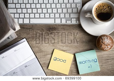 Digital tablet computer with sticky note paper and cup of coffee on old wooden desk. Simple workspace or coffee break in morning